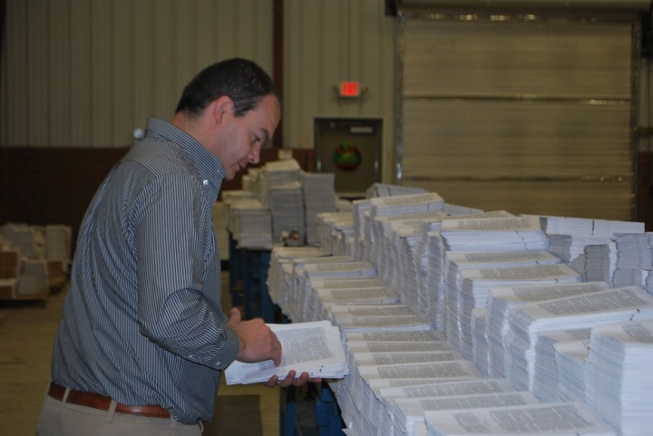 Shannon Lemmon collates pages for a Bible at Bible & Literature Missionary Foundation.